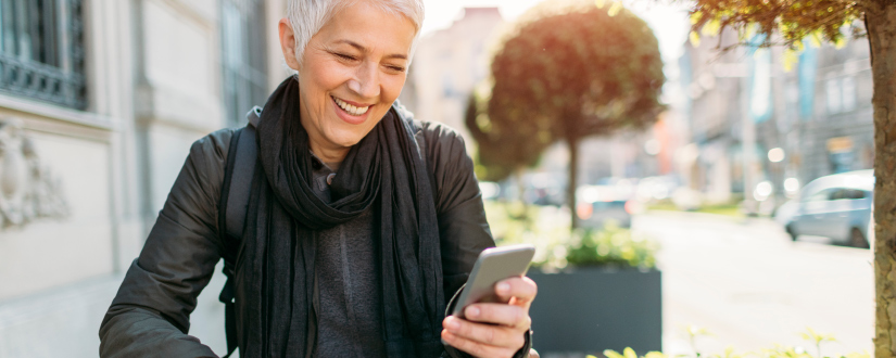 woman smiling while looking at mobile phone